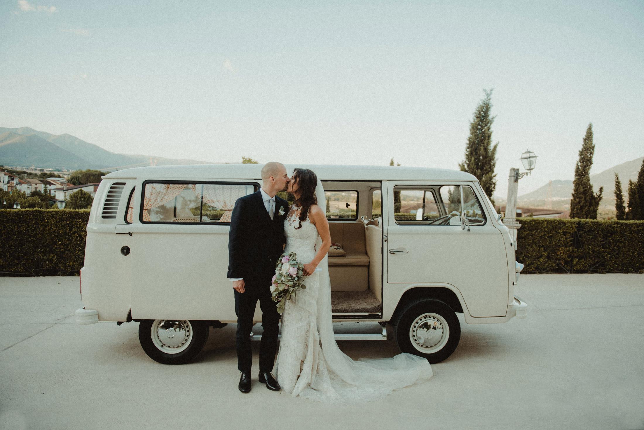 Hochzeitspaar küsst sich vor einem weißen VW Bus