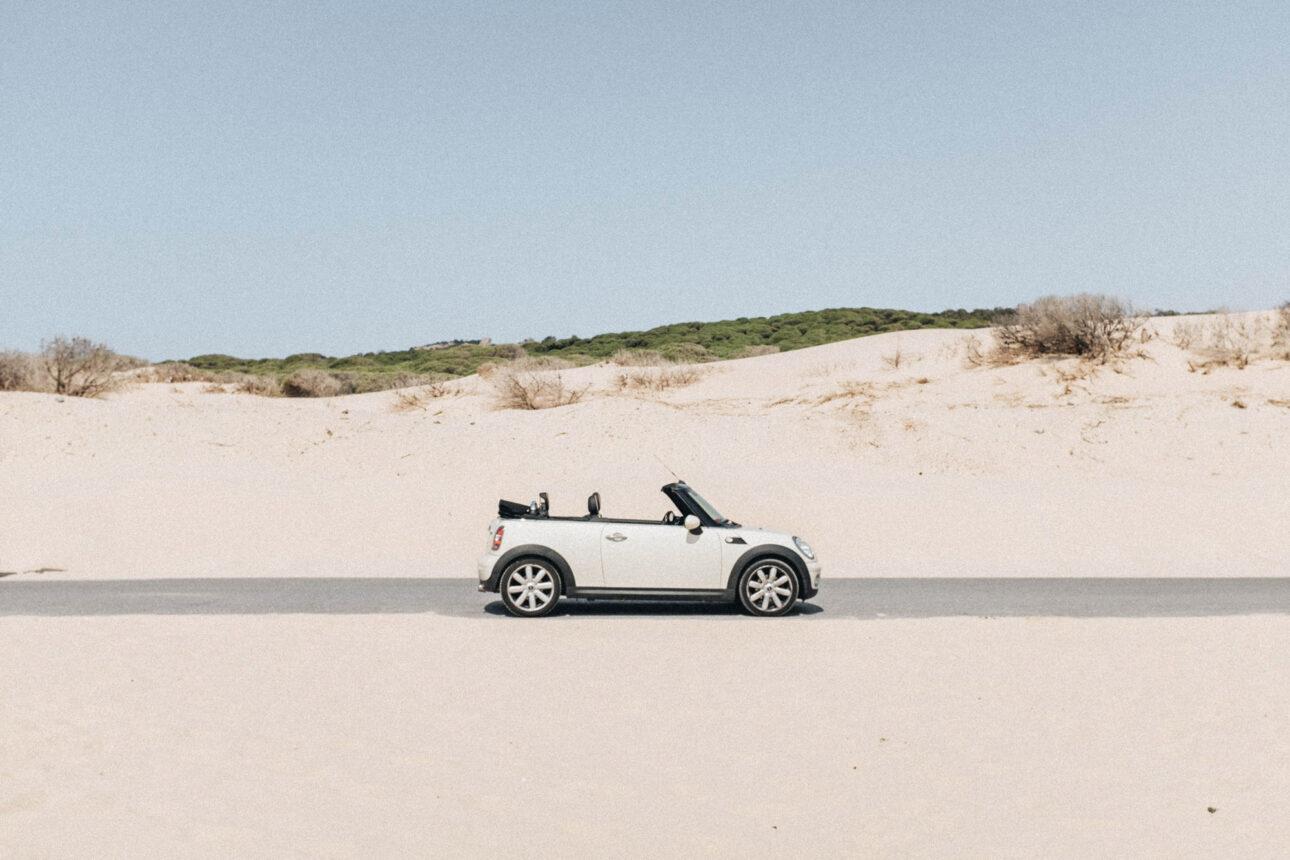 weißer Mini Cabrio fährt auf einer Straße in den Dünen